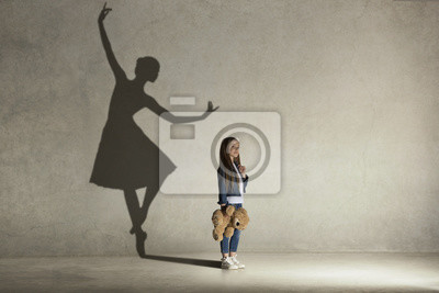 Bild Baby girl dreaming about dancing ballet. Childhood and dream concept. Conceptual image with shadow of ballerina on the studio wall