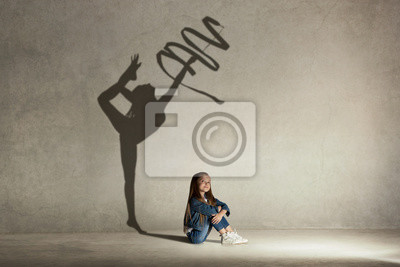 Bild Baby girl dreaming about gymnast profession. Childhood and dream concept. Conceptual image with shadow of female gymnast on the studio wall