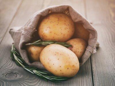 Bild Baby-Kartoffeln in Sack Tasche mit Rosmarin auf Holztisch, Vintage getönten