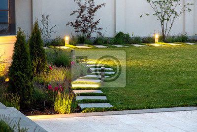Bild backyard of the mansion with a flowerbed and a lawn of green grass with a marble walkway of square tiles in the evening with a garden lighting with decorative ground lamps illuminating a warm light.