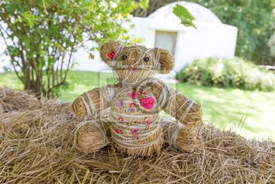Bär Puppe sitzt auf trockenem Stroh