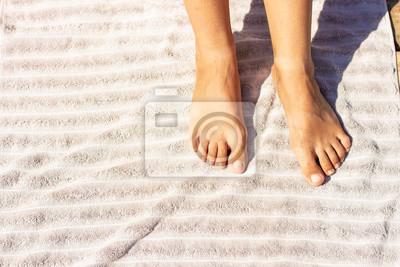 Bild bare child female feet on gray towel textile texture background