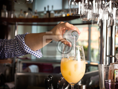Bild Bartender's hand holding a botlle with alcohol drink and puring it into the orange cocktail.