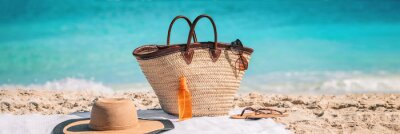 Bild Beach essentials for summer vacation: straw bag with sunglasses, sunscreen, hat banner background. What to bring for holiday getaway.