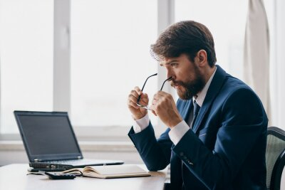 Bild bearded man sitting at a desk in front of a laptop stress anger official