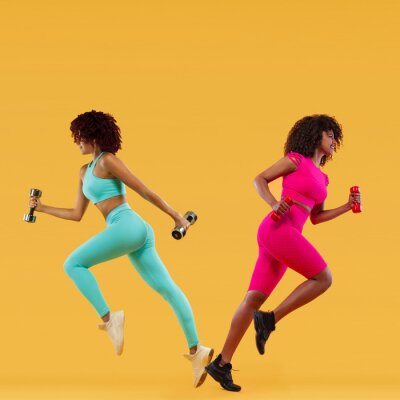 Beautiful African American and caucasian women running. Two strong athletic, women sprinter or runner on yellow background with dumbbells wearing color sportswear. Fitness and sport motivation.
