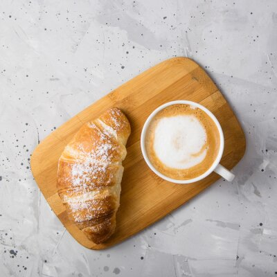 Bild Beautiful and simple traditional French breakfast of fresh croissant and a cup of cappuccino