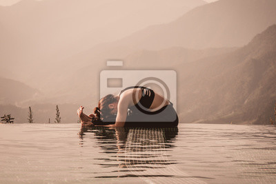 Beautiful Asian woman practice yoga sitting forward fold pose on the pool above the Mountain peak in the morning in front of beautiful nature views,Feel so comfortable and relax with yoga in holiday