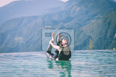 Beautiful Attractive Asian woman practice yoga bow or dhanurasana pose on the pool above the Mountain peak in the morning in front of beautiful nature views in SAPA vietnam,Feel so comfortable
