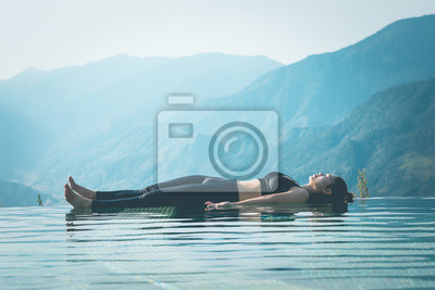 Beautiful Attractive Asian woman practice yoga Dead Body or Savasana on the pool above the Mountain peak in the morning in front of beautiful nature views in SAPA vietnam,Feel so comfortable