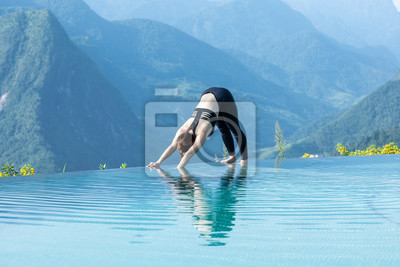 Beautiful Attractive Asian woman practice yoga Downward Facing Dog or Adho Mukha Svanasana pose on the pool above the Mountain peak in the morning in front of beautiful nature views in SAPA vietnam