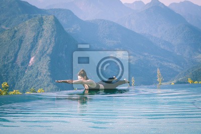 Beautiful Attractive Asian woman practice yoga Locust or Shalabhasana pose on the pool above the Mountain peak in the morning in front of beautiful nature views in SAPA vietnam