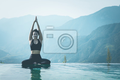 Beautiful Attractive Asian woman practice yoga Lotus pose on the pool above the Mountain peak in the morning in front of beautiful nature views in SAPA vietnam,Feel so comfortable and relax in holiday