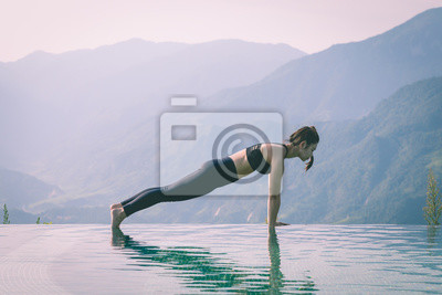Beautiful Attractive Asian woman practice yoga Plank or Phalakasana Pose on the pool above the Mountain peak in the morning in front of beautiful nature views in SAPA vietnam,Feel so comfortable