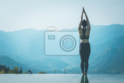Beautiful Attractive Asian woman practice yoga Surya Namaskar exercise Ekam pose on the pool above the Mountain peak in the morning in front of beautiful nature views in SAPA vietnam,Feel comfortable
