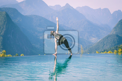 Beautiful Attractive Asian woman practice yoga Triangle pose or Utthita Trikonasana pose on the pool above the Mountain peak in the morning in front of beautiful nature views in SAPA vietnam