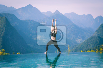 Beautiful Attractive Asian woman practice yoga Warrior I or Virabhadrasana Pose on the pool above the Mountain peak in the morning in front of beautiful nature views in SAPA vietnam
