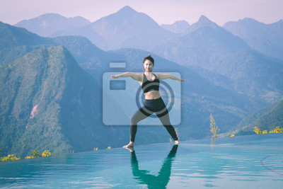 Beautiful Attractive Asian woman practice yoga warrior or Virabhadrasana Pose on the pool above the Mountain peak in the morning in front of beautiful nature views in SAPA vietnam,Feel so comfortable