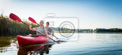 Bild Beautiful couple sailing kayak on lake