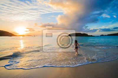 Bild Beautiful girl wearing a bikini walking out of the ocean at sunset in Cinnamon Bay, St. John, USVI