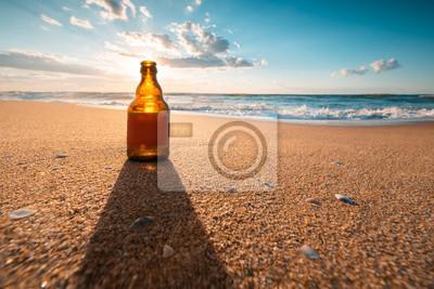Beautiful sea sunrise and beer bottle on the beach sand