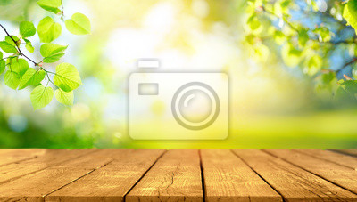 Bild Beautiful spring background with green juicy young foliage and empty wooden table in nature outdoor. Natural template with Beauty bokeh and sunlight.