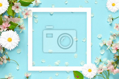 Bild Beautiful spring nature background with lovely blossom, petal a on turquoise blue background , top view, frame. Springtime concept.