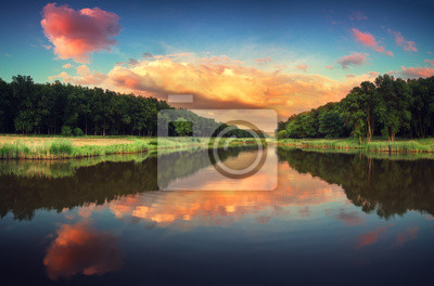 Beautiful summer sunset at the river with reflection