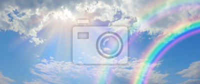Bild Beautiful vibrant double rainbow Cloudscape Background - awesome blue sky with pretty clouds, bright sun shining down and a large double rainbow arcing across the right corner with copy space