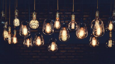 Bild Beautiful vintage luxury light bulb hanging decor glowing in dark. Retro filter effect style.