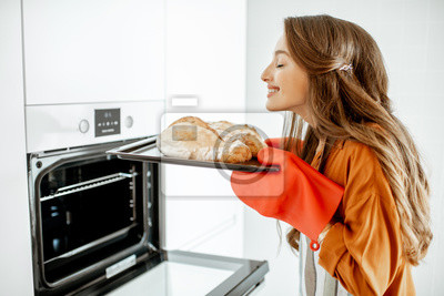 Bild Beautiful young woman baking bread in the oven at the modern white kitchen at home