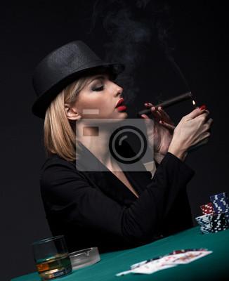 Bild Beautiful young woman smokes a cigar during a poker game