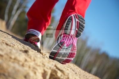 Beine eines Mädchens in Turnschuhen
