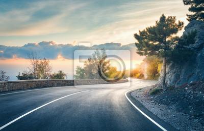 Bild Bergstraße. Landschaft mit Felsen, sonniger Himmel mit Wolken und schöne asphaltierte Straße am Abend im Sommer. Vintage Tönung. Reisehintergrund Autobahn in den Bergen. Transport