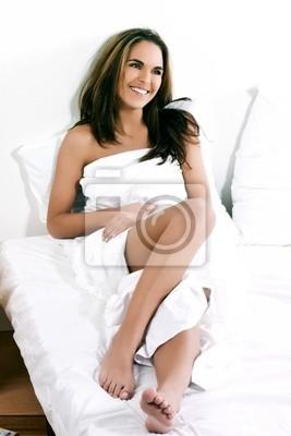beuatiful kaukasischen Frau liegt auf einem weißen Bett lächelnd