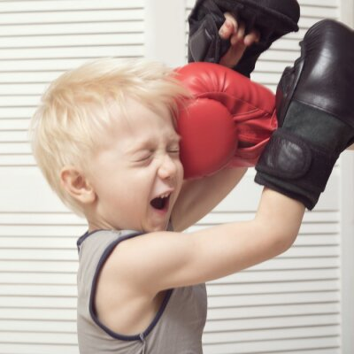 Blond boy boxing with hand in red glove. Blow in the face