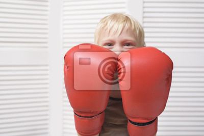 Blond boy is protected in two boxing gloves. Portrait