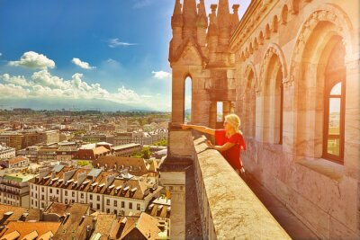 Bild Blonde tourist girl pointed rooftops of Geneva skyline from height of the north tower of Cathedral Gothic Romanesque of Saint-Pierre, French Swiss in Switzerland. Sunset light between mountains.