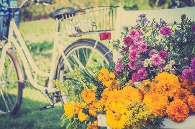 Bild Blumenstrauß auf einem weißen Stuhl. Unscharfes Retro- Fahrrad im Hintergrund.