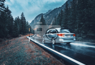Bild Blurred car in motion on the road in autumn forest in rain. Perfect asphalt mountain road in overcast rainy day. Roadway, pine trees in italian alps. Transportation. Highway in foggy woodland. Travel