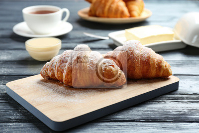 Bild Board with tasty croissants on dark wooden table. French pastry
