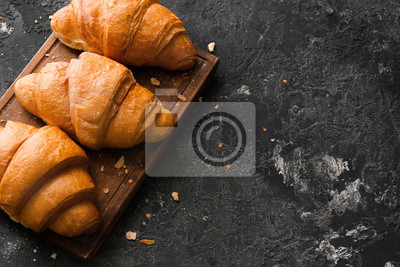 Bild Board with tasty croissants on grey textured background