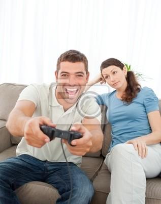 Bored Frau schaut auf ihren Freund Wiedergabe von Video-Spiel auf dem s
