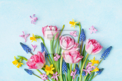 Bild Bouquet of beautiful spring flowers on pastel blue table top view. Greeting card for International Women Day. Flat lay.