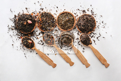 Bild Bowls and spoons with different types of dry tea leaves on white background