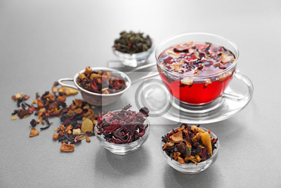 Bild Bowls with different types of dry tea leaves and cup of aromatic beverage on light background