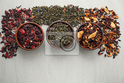 Bild Bowls with different types of dry tea leaves on light background