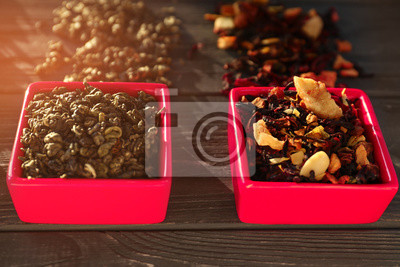 Bild Bowls with different types of dry tea leaves on wooden background