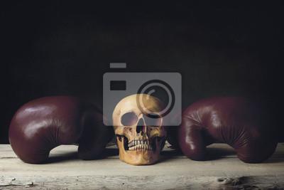 Boxhandschuhe mit menschlicher Schädel, der auf hölzernen Planken