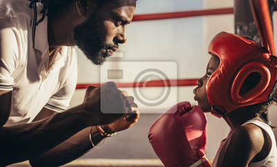 Bild Boxing trainer teaching a kid about boxing